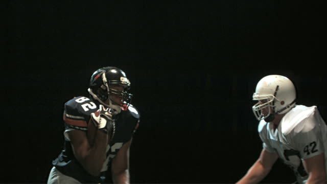slo mo ms studio shot of two american football players in action - 対決点の映像素材/bロール