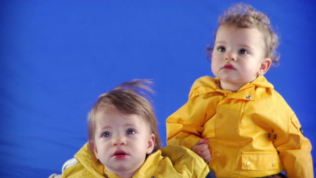 cu studio shot of two baby girls (12-17, 18-23 months)  in raincoats on blue screen - 12 23 mesi video stock e b–roll