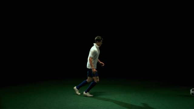 SLO MO WS Studio shot of two football players in action