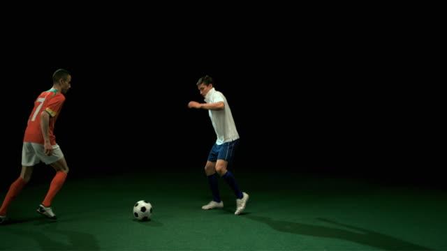 slo mo ws studio shot of two football players kicking ball - ライバル点の映像素材/bロール