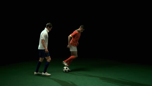 slo mo ws studio shot of two football players kicking ball - fotboll lagsport bildbanksvideor och videomaterial från bakom kulisserna