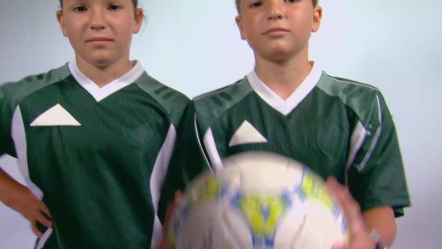 Studio shot of two girls in soccer uniforms