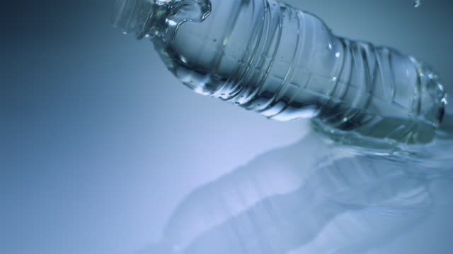 slo mo cu studio shot of water bottle falling in water - man made object stock videos & royalty-free footage
