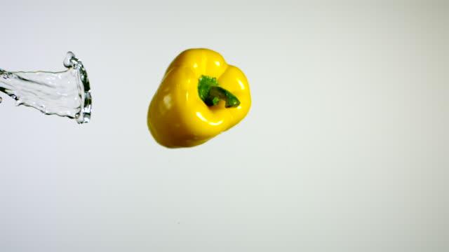 SLO MO CU Studio shot of water splashing on yellow bell pepper