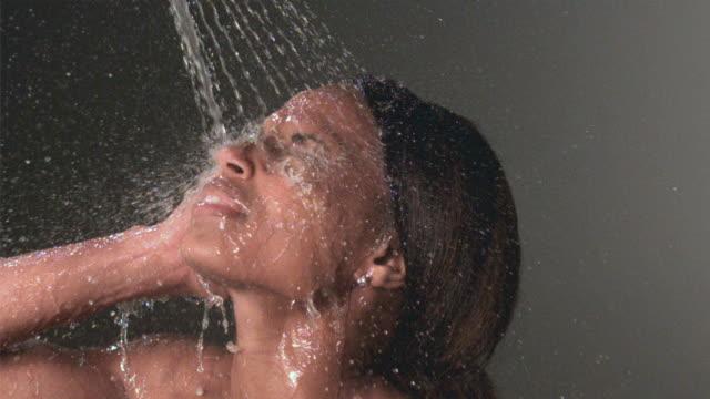 vídeos y material grabado en eventos de stock de slo mo cu studio shot of water spraying on woman's face - ducha