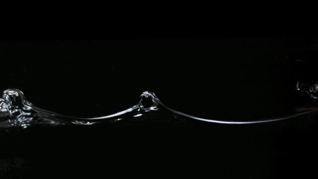 SLO MO CU Studio shot of water wave against black background