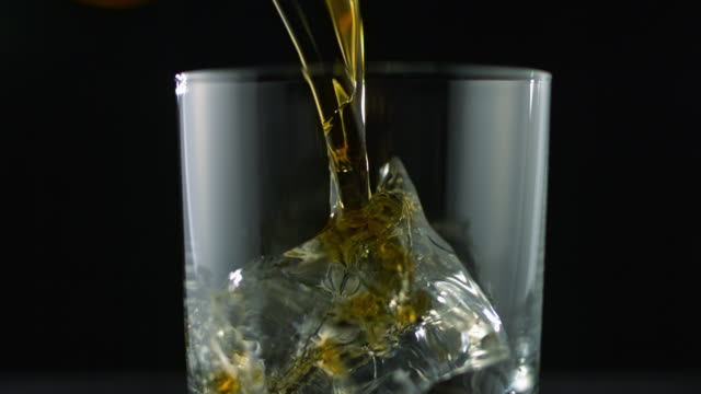 SLO MO MS Studio shot of whiskey being poured into glass with ice cubes on black background