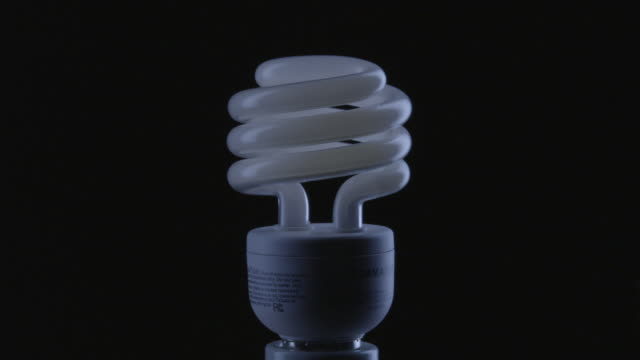 cu studio shot of white fluorescent light bulb - light bulb stock videos and b-roll footage