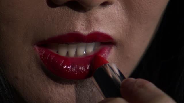 ecu studio shot of woman applying lipstick / orem, utah, usa - 自己改善点の映像素材/bロール