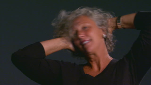 studio shot of woman fluffing hair - capelli grigi video stock e b–roll