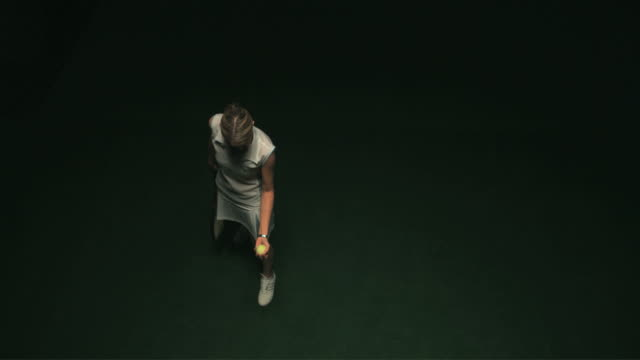 SLO MO WS HA Studio shot of woman serving tennis ball