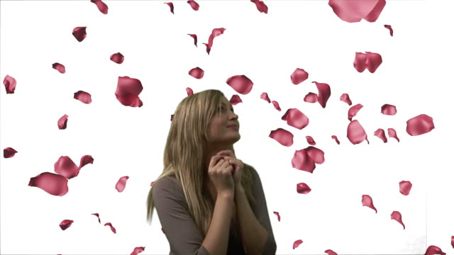 cu, composite, studio shot of woman surrounded with falling rose petals - ストレートヘア点の映像素材/bロール