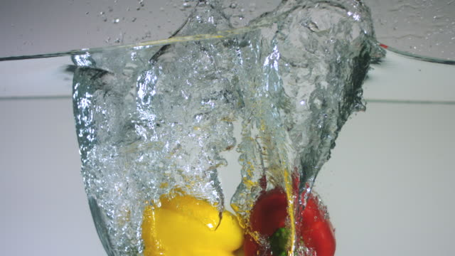SLO MO CU Studio shot of yellow and red bell peppers falling into water