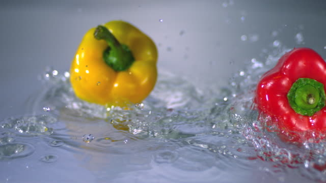 SLO MO CU FOCUSING Studio shot of yellow and red bell peppers rotating in water