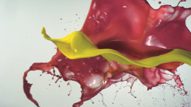 SLO MO, CU, Studio shot of yellow and red paint splashing