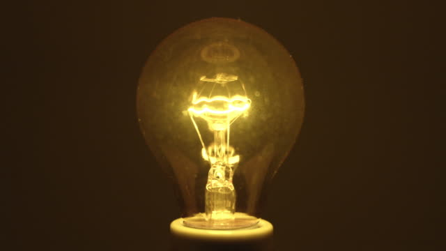 cu focusing studio shot of yellow incandescent light bulb - filament stock videos & royalty-free footage