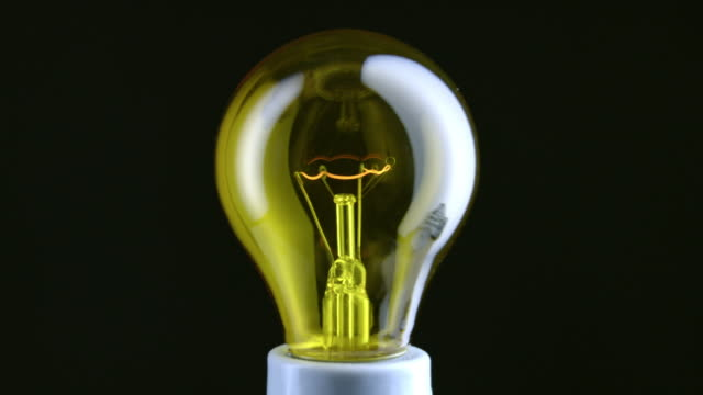 cu studio shot of yellow incandescent light bulb - filament stock videos & royalty-free footage