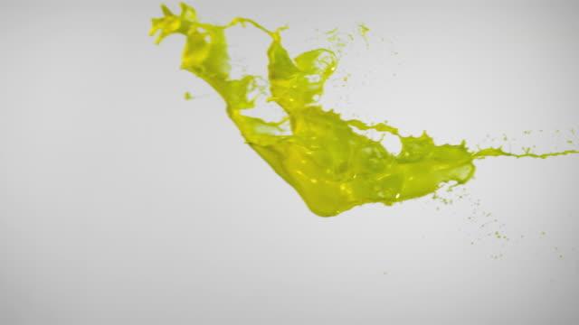 SLO MO, CU, Studio shot of yellow paint splashing