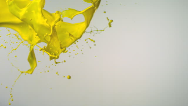 vídeos de stock e filmes b-roll de slo mo, cu, studio shot of yellow paint splashing - cores