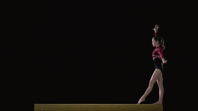 stockvideo's en b-roll-footage met slo mo ms studio shot of young rhythmic gymnast jumping on balance beam - gymnastiek