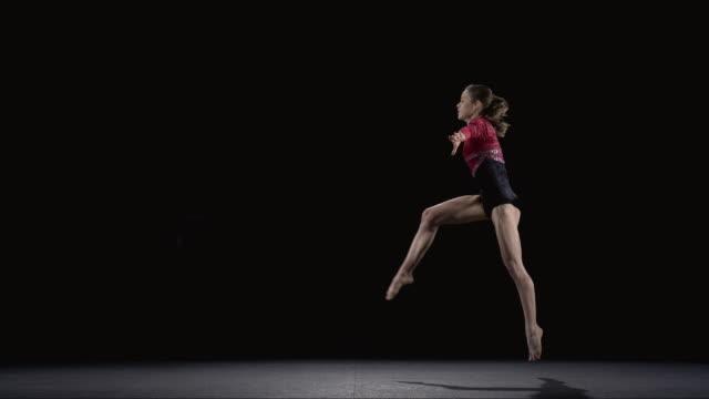 vídeos de stock, filmes e b-roll de slo mo ws studio shot of young rhythmic gymnast jumping - acrobata