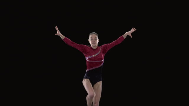 SLO MO MS Studio shot of young rhythmic gymnast jumping