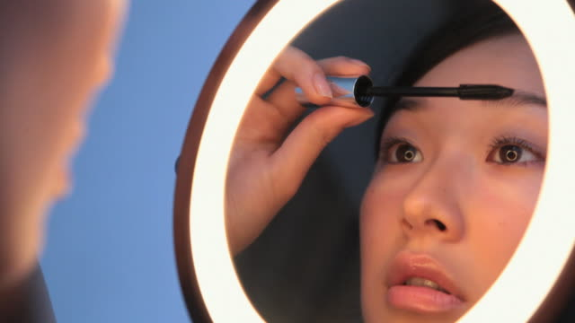 CU Studio shot of young woman applying mascara in front of mirror