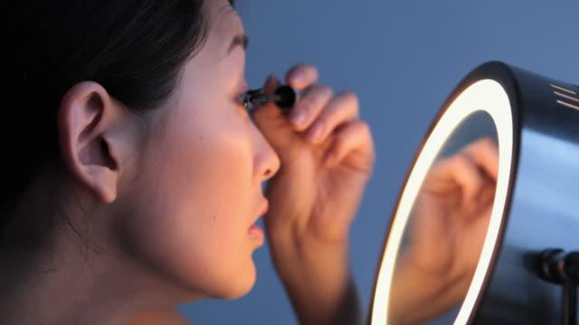 CU ZI ZO Studio shot of young woman applying mascara in front of mirror