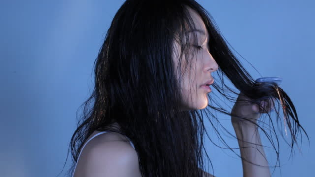 cu studio shot of young woman combing wet hair - wet hair stock videos and b-roll footage