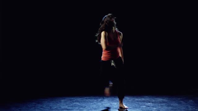 WS Studio shot of young woman dancing