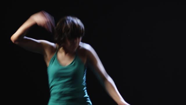 ms studio shot of young woman dancing - ノースリーブトップ点の映像素材/bロール