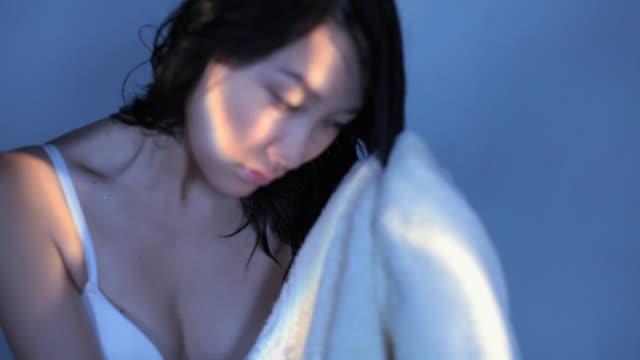 cu studio shot of young woman drying her hair with towel - ヘアケア点の映像素材/bロール