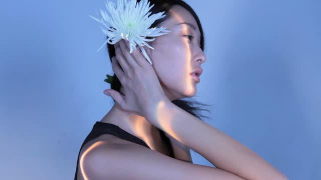 vídeos y material grabado en eventos de stock de cu studio shot of young woman holding and smelling chrysanthemum flower - crisantemo