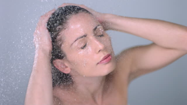 slo mo cu ha studio shot of young woman in shower - washing hair stock videos & royalty-free footage
