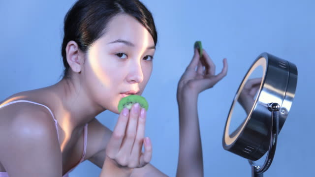 cu studio shot of young woman placing kiwi slices on eyes in front of mirror - hair bun stock videos and b-roll footage