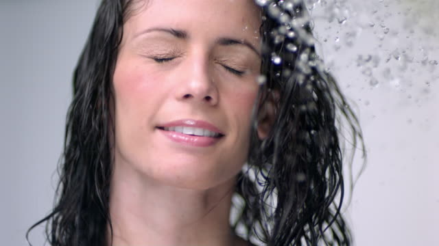 slo mo cu studio shot of young woman shaking head in shower - wet hair stock videos and b-roll footage