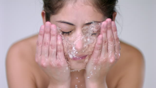 slo mo cu studio shot of young woman washing face - washing face stock videos & royalty-free footage