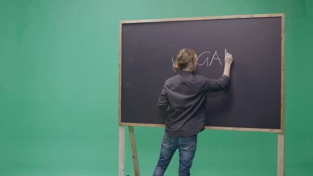 studio, slow motion, green screen, young male teacher writes on a blackboard, london, uk - dreiviertelansicht stock-videos und b-roll-filmmaterial