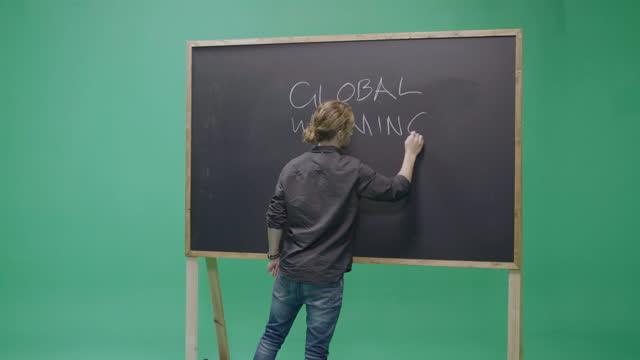 vidéos et rushes de studio, slow motion, green screen, young male teacher writes on a blackboard, london, uk - cadrage aux genoux