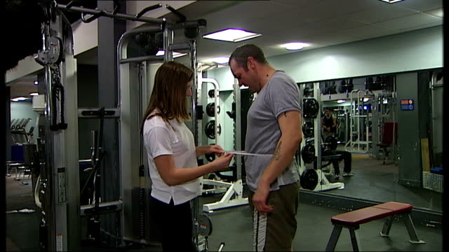 vídeos de stock e filmes b-roll de study links waistline measurement to risk of premature death; england: london: int general views of woman measuring man's waist and hips inside gym - cintura