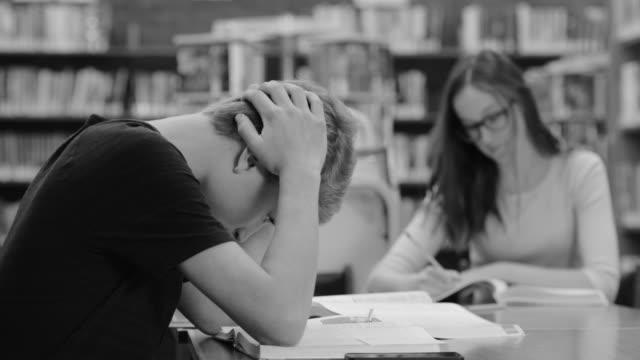 stockvideo's en b-roll-footage met studeren in bibliotheek b&w - plusteken