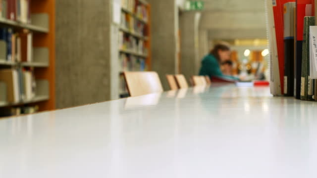 studying in library (selective focus) - hardcover book stock videos and b-roll footage