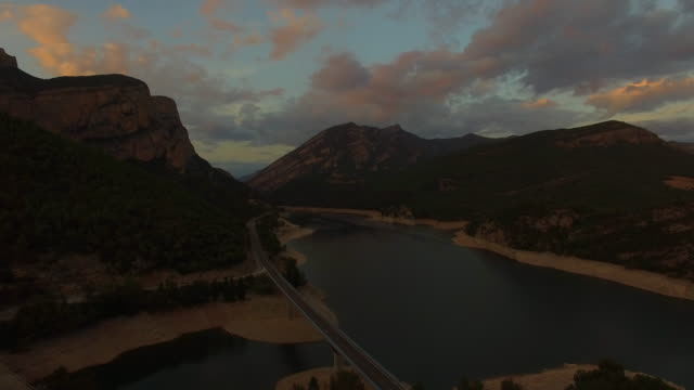 Stunning aerial footage recorded with drone flying over a cool landscape in the Catalan Pyrenees with cars on the road near the reservoir during the sunset time of the day. 4K UHD.