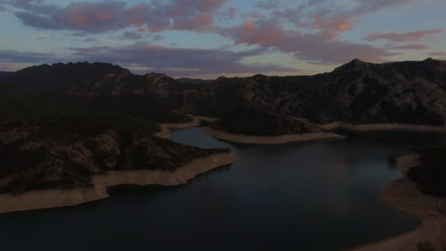 Stunning aerial footage recorded with drone flying over a cool landscape in the Catalan Pyrenees with water reservoir in low level after summer, sustainable resource and renewable energy. 4K UHD.