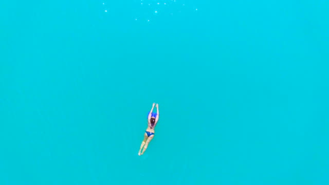 vídeos de stock, filmes e b-roll de stunning aerial footage recorded with drone flying over a woman swimming in a beautiful turquoise water lake in the catalan pyrenees during travel vacations in the mountains. 4k uhd. - menos zoom