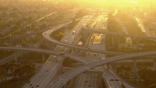 stunning aerial shot of a los angeles freeway interchange bathed in afternoon sunlight. - straßenüberführung stock-videos und b-roll-filmmaterial