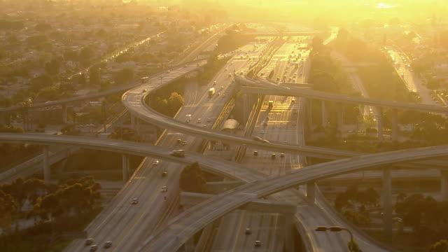 stunning aerial shot of a los angeles freeway interchange bathed in afternoon sunlight. - kalifornien stock-videos und b-roll-filmmaterial