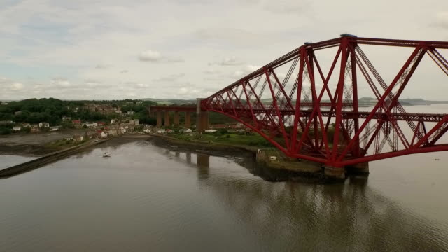 vídeos y material grabado en eventos de stock de stunning aerial shot of the forth rail bridge during the day in south queensferry - río firth of forth
