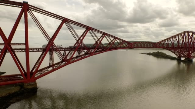 stunning aerial shot of the forth rail bridge during the day in south queensferry with a local train passing - maroon stock videos and b-roll footage