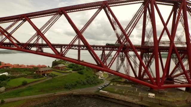 stunning aerial shot of the forth rail bridge during the day in south queensferry with a steam train passing by - fluss firth of forth stock-videos und b-roll-filmmaterial